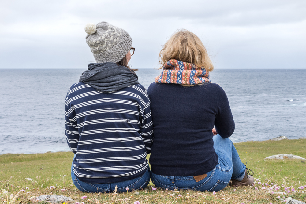 Ella wears a Fair Isle Watch Cap while Vivian sports a cowl. They sit on a high bank overlooking the Atlantic Ocean